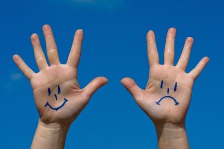 cabizbajo: Manos con sonrisas y el patr?n de tristeza contra el cielo azul
