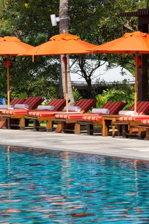 Beach chairs near swimming pool in tropical resort , Thailand. photo