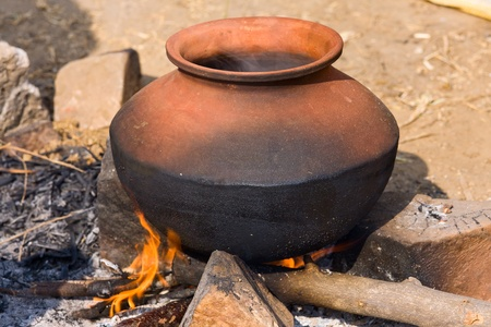 ingenuity: Clay pot with food on fire, India