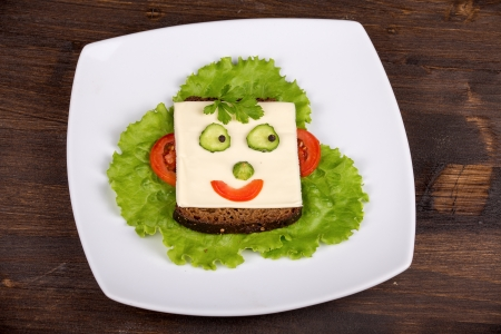 Fun food for kids - face on bread, made from cheese, lettuce, tomato, cucumber and pepper. photo