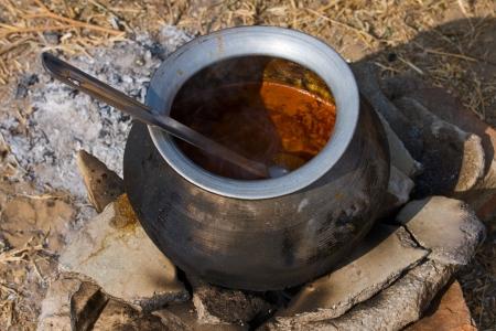 ingenuity: Metal  pot with food on fire, Pushkar, India Stock Photo