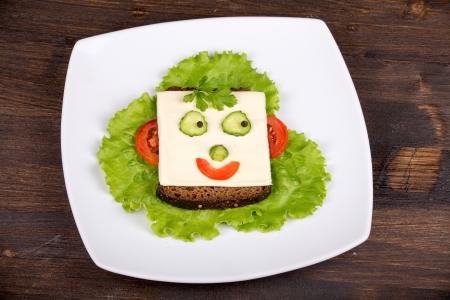 breakfast smiley face: Fun food for kids - face on bread, made from cheese, lettuce, tomato, cucumber and pepper. Stock Photo