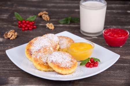 Cheese pancakes with honey and berry jam in white plate photo