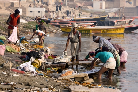 VARANASI, INDIA - DECEMBER 1: Unidentified Indian people wash clothes in Ganga river on  December 1, 2012 in Varanasi, India. For many dwellers of Varanasi the Ganga is only way to wash clothes. Stock Photo - 22383463