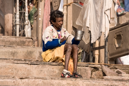 squalor: VARANASI, INDIA - DECEMBER 1: An unidentified crippled man sits on the ghat along the Ganges begging for money on December 1, 2012 in Varanasi, India.