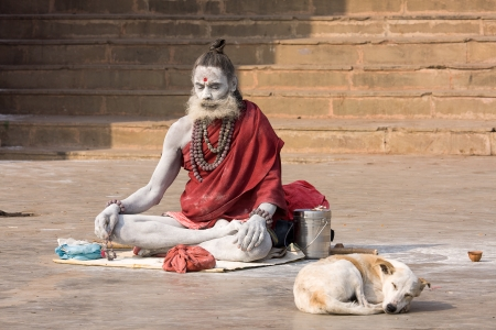 VARANASI, INDIA - DECEMBER 1: An unidentified sadhu sits on the ghat along the Ganges on December 1, 2012 in Varanasi, India. Tourism has drawn many alleged fake sadhus to Varanasi Stock Photo - 22450767