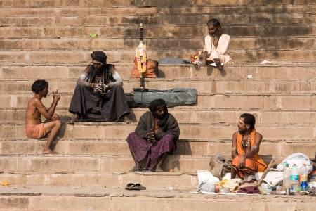 VARANASI, INDIA - DECEMBER 1: An unidentified sadhu and man sits on the ghat along the Ganges on December 1, 2012 in Varanasi, India. Tourism has drawn many alleged fake sadhus to Varanasi Stock Photo - 22460461
