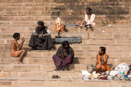 VARANASI, INDIA - DECEMBER 1: An unidentified sadhu and man sits on the ghat along the Ganges on December 1, 2012 in Varanasi, India. Tourism has drawn many alleged fake sadhus to Varanasi Stock Photo - 22460461