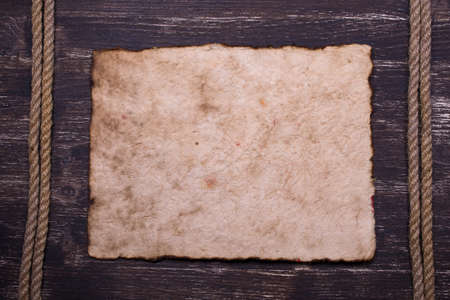 piece of paper: Old burnt paper on wood with rope frame background Stock Photo