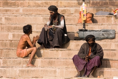 pauper: VARANASI, INDIA - DECEMBER 1: An unidentified sadhu and man sits on the ghat along the Ganges on December 1, 2012 in Varanasi, India. Tourism has drawn many alleged fake sadhus to Varanasi Editorial