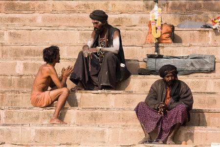 VARANASI, INDIA - DECEMBER 1: An unidentified sadhu and man sits on the ghat along the Ganges on December 1, 2012 in Varanasi, India. Tourism has drawn many alleged fake sadhus to Varanasi Stock Photo - 22541483