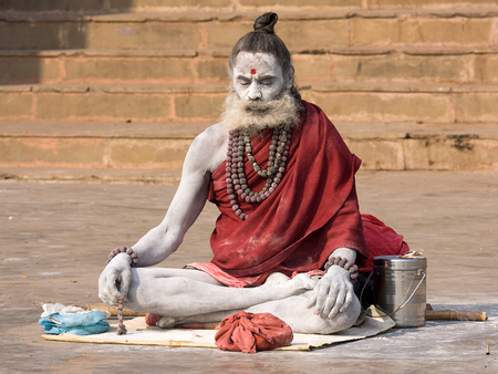 VARANASI, INDIA - DECEMBER 1: An unidentified sadhu sits on the ghat along the Ganges on December 1, 2012 in Varanasi, India. Tourism has drawn many alleged fake sadhus to Varanasi Stock Photo - 22541484