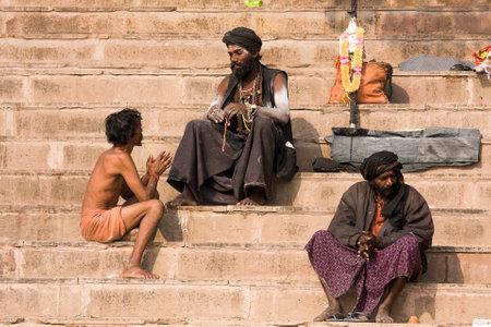 VARANASI, INDIA - DECEMBER 1: An unidentified sadhu and man sits on the ghat along the Ganges on December 1, 2012 in Varanasi, India. Tourism has drawn many alleged fake sadhus to Varanasi Stock Photo - 22579426