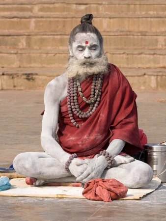 VARANASI, INDIA - DECEMBER 1: An unidentified sadhu sits on the ghat along the Ganges on December 1, 2012 in Varanasi, India. Tourism has drawn many alleged fake sadhus to Varanasi Stock Photo - 22579427