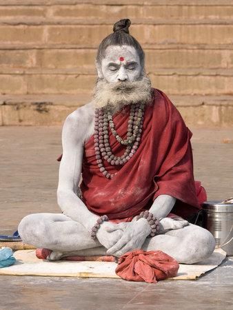 VARANASI, INDIA - DECEMBER 1: An unidentified sadhu sits on the ghat along the Ganges on December 1, 2012 in Varanasi, India. Tourism has drawn many alleged fake sadhus to Varanasi Stock Photo - 22579427