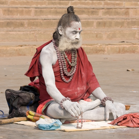 VARANASI, INDIA - DECEMBER 1: An unidentified sadhu sits on the ghat along the Ganges on December 1, 2012 in Varanasi, India. Tourism has drawn many alleged fake sadhus to Varanasi Stock Photo - 22716638