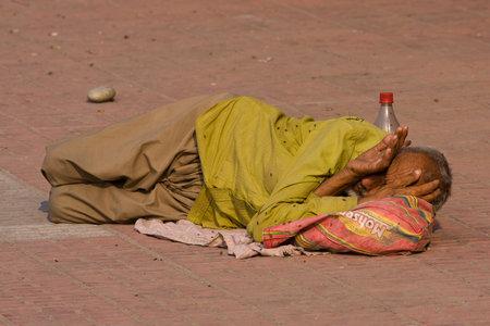 squalor: HARIDWAR, INDIA - NOV 8: An unidentified homeless man sleeps on the sidewalk near the River Ganges on November 8, 2012 in Haridwar, India. Poor Indians flock to Haridwar for charity.