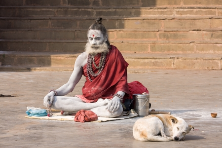 VARANASI, INDIA - DECEMBER 1: An unidentified sadhu sits on the ghat along the Ganges on December 1, 2012 in Varanasi, India. Tourism has drawn many alleged fake sadhus to Varanasi Stock Photo - 22746332