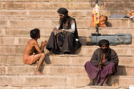 VARANASI, INDIA - DECEMBER 1: An unidentified sadhu and man sits on the ghat along the Ganges on December 1, 2012 in Varanasi, India. Tourism has drawn many alleged fake sadhus to Varanasi Stock Photo - 22793161