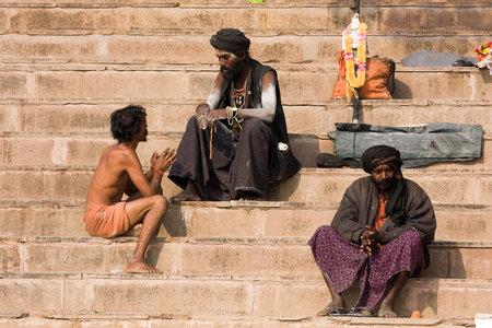 VARANASI, INDIA - DECEMBER 1: An unidentified sadhu and man sits on the ghat along the Ganges on December 1, 2012 in Varanasi, India. Tourism has drawn many alleged fake sadhus to Varanasi Stock Photo - 22793161