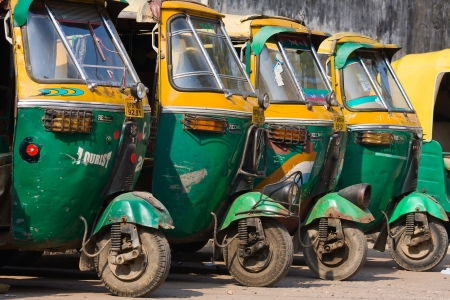 auto rickshaw: AGRA, INDIA - NOVEMBER 26: Auto rickshaw taxis on a road on November 26, 2012 in Agra, India. These iconic taxis have recently been fitted with CNG powered engines in an effort to reduce pollution