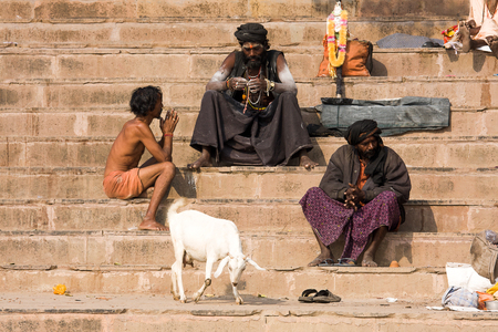VARANASI, INDIA - DECEMBER 1: An unidentified sadhu and man sits on the ghat along the Ganges on December 1, 2012 in Varanasi, India. Tourism has drawn many alleged fake sadhus to Varanasi Stock Photo - 23136435