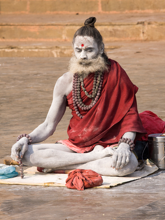 VARANASI, INDIA - DECEMBER 1: An unidentified sadhu sits on the ghat along the Ganges on December 1, 2012 in Varanasi, India. Tourism has drawn many alleged fake sadhus to Varanasi