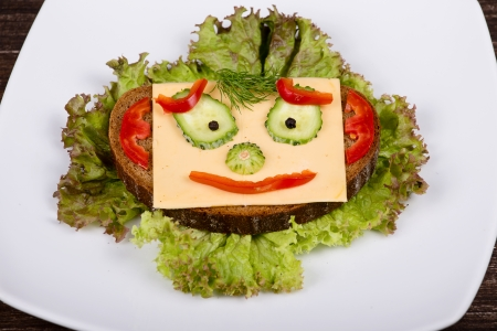 breakfast smiley face: Fun food for kids - face on bread, made from cheese, lettuce, tomato, cucumber and pepper