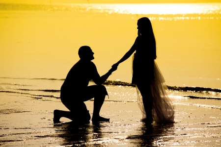 Bride and groom on the beach during sunset photo
