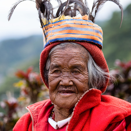 BANAUE - JANUARY 24 : Unknown old ifugao woman in national dress next to rice terraces on January 24, 2014 in Banaue, Philippines. Ifugao - the people in the Philippines. Refers to the mountain peoples.