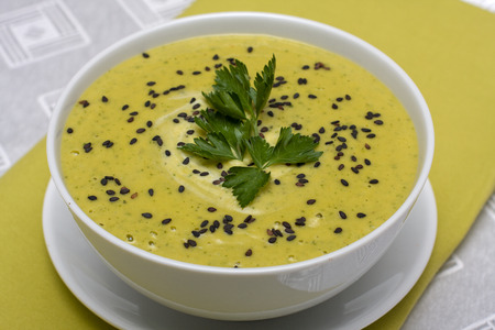 Spinach cream soup in white bowl, close up photo