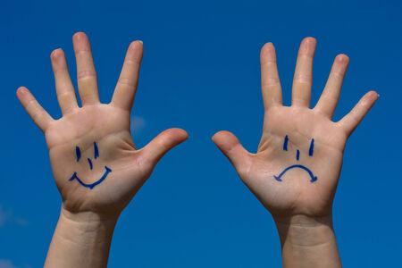 crestfallen: Manos con sonrisas y el patr�n de tristeza contra el cielo azul