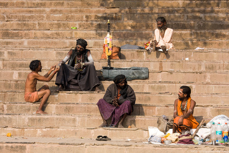 alleged: VARANASI, INDIA - DECEMBER 1: An unidentified sadhu and man sits on the ghat along the Ganges on December 1, 2012 in Varanasi, India. Tourism has drawn many alleged fake sadhus to Varanasi Editorial