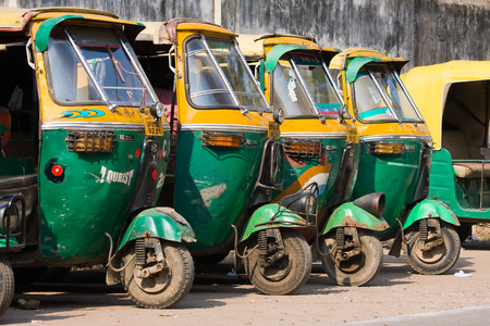 auto rickshaw: AGRA, INDIA - NOVEMBER 26, 2012 : Auto rickshaw taxis on a road in Agra, India. These iconic taxis have recently been fitted with CNG powered engines in an effort to reduce pollution
