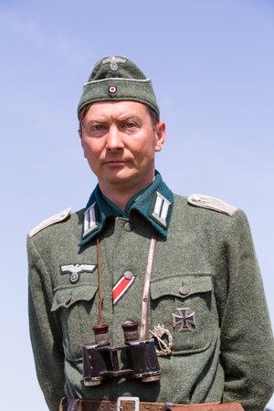 nazi flag: KIEV, UKRAINE -MAY 11: Member of Red Star history club wears historical German uniform during historical reenactment of WWII, May 11, 2013 in Kiev, Ukraine