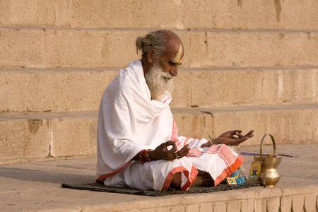 VARANASI, INDIA - DECEMBER 1: An unidentified sadhu sits on the ghat along the Ganges on December 1, 2012 in Varanasi, India. Tourism has drawn many alleged fake sadhus to Varanasi Stock Photo - 29099797