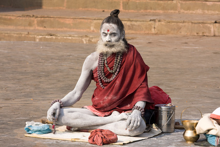 alleged: VARANASI, INDIA - DECEMBER 1: An unidentified sadhu sits on the ghat along the Ganges on December 1, 2012 in Varanasi, India. Tourism has drawn many alleged fake sadhus to Varanasi