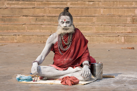 VARANASI, INDIA - DECEMBER 1: An unidentified sadhu sits on the ghat along the Ganges on December 1, 2012 in Varanasi, India. Tourism has drawn many alleged fake sadhus to Varanasi Stock Photo - 29099808