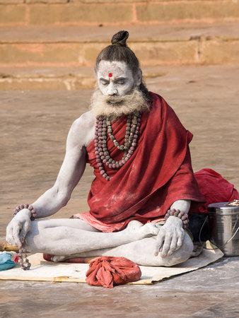 VARANASI, INDIA - DECEMBER 1, 2012 : An unidentified sadhu sits on the ghat along the Ganges river. Tourism has drawn many alleged fake sadhus to Varanasi Stock Photo - 29153185