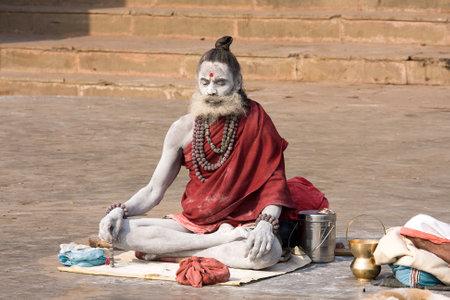 VARANASI, INDIA - DECEMBER 1, 2012 : An unidentified sadhu sits on the ghat along the Ganges river. Tourism has drawn many alleged fake sadhus to Varanasi Stock Photo - 29280567