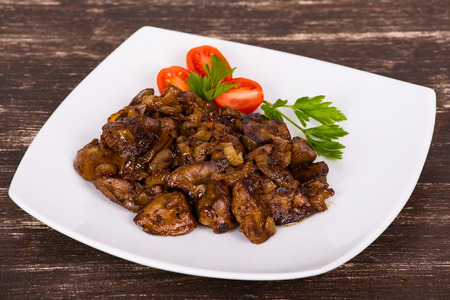 innards: Chicken livers in a creamy sauce with onion on white plate Stock Photo