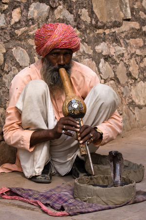 JAIPUR, INDIA - NOVEMBER 10, 2012: An unidentified snake charmer is playing the flute for the cobra sitting by the wall in the Fort Amber in Jaipur, India