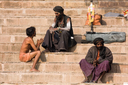 VARANASI, INDIA - DECEMBER 1, 2012 : An unidentified sadhu sits on the ghat along the Ganges river. Tourism has drawn many alleged fake sadhus to Varanasi Stock Photo - 29477897