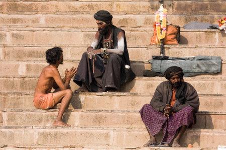 VARANASI, INDIA - DECEMBER 1, 2012 : An unidentified sadhu sits on the ghat along the Ganges river. Tourism has drawn many alleged fake sadhus to Varanasi Stock Photo - 29477897