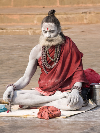 alleged: VARANASI, INDIA - DECEMBER 1, 2012 : An unidentified sadhu sits on the ghat along the Ganges river. Tourism has drawn many alleged fake sadhus to Varanasi