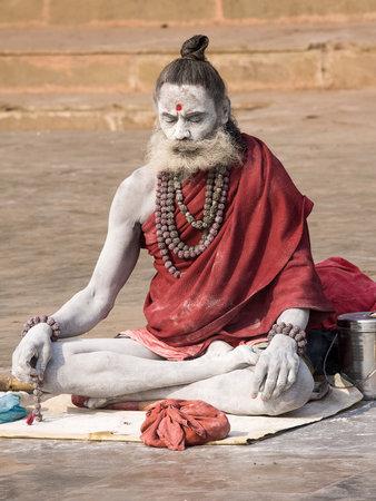 VARANASI, INDIA - DECEMBER 1, 2012 : An unidentified sadhu sits on the ghat along the Ganges river. Tourism has drawn many alleged fake sadhus to Varanasi Stock Photo - 29477895