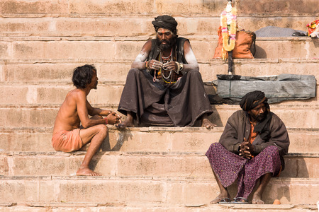 VARANASI, INDIA - DECEMBER 1, 2012 : An unidentified sadhu sits on the ghat along the Ganges river. Tourism has drawn many alleged fake sadhus to Varanasi