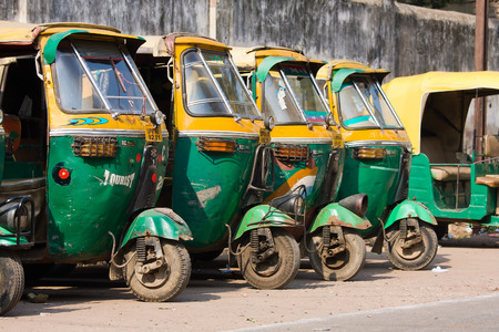 AGRA, INDIA - NOVEMBER 26, 2012: Auto rickshaw taxis on a road in Agra, India. These iconic taxis have recently been fitted with CNG powered engines in an effort to reduce pollution Editorial