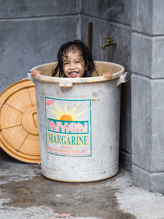penury: LEGAZPI, PHILIPPINES - MARCH 18, 2014: Unidentified homeless girl bathes in a plastic bucket of margarine. Nearly one of every three Filipino children aged 4 to 10 is underweight