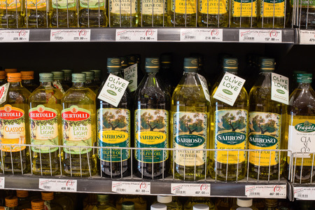 food shelf: BANGKOK,THAILAND - NOVEMBER 19, 2013:Selection of olive oil on the shelves in a supermarket Siam Paragon. With 300,000 sqm of retail space Siam Paragon is one of the worlds largest malls
